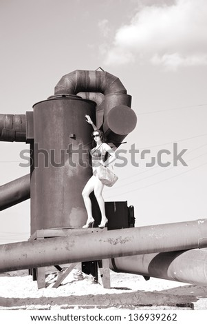 attractive woman on rusty old metal construction - stock photo