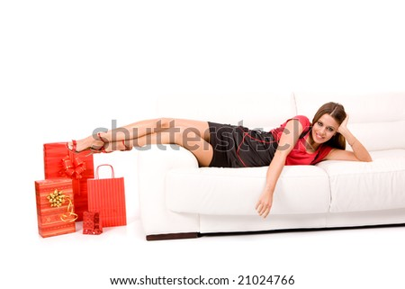 Attractive woman  on sofa with present. - stock photo