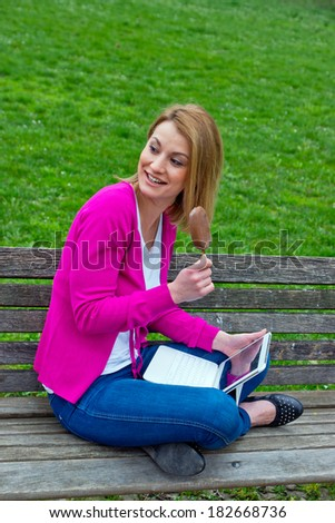 attractive woman on the park bench with laptop and ice cream