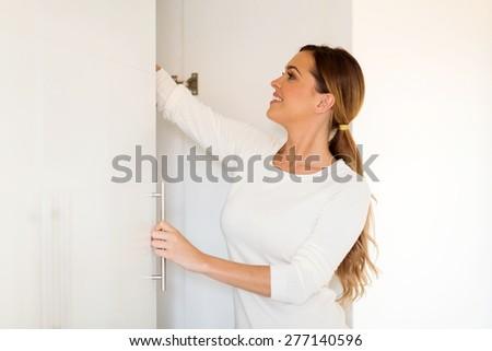 attractive woman opening wardrobe doors - stock photo
