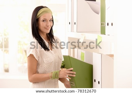 Attractive woman packing folders on shelf, smiling at camera.? - stock photo