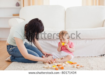 Attractive woman playing with her baby in while sitting on a carpet in the living room - stock photo