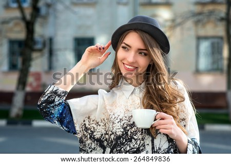 attractive woman poses with white cup. happy smile girl drink coffee or tea hold cup.  city background - stock photo