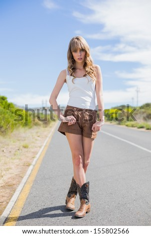 Attractive woman posing while hitchhiking on a deserted road in summertime - stock photo