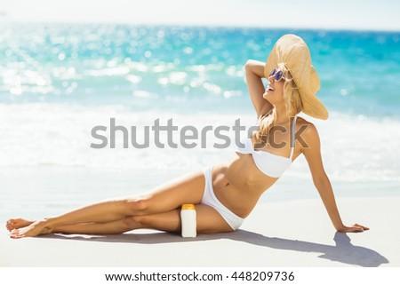 Attractive woman posing with sun cream on beach - stock photo