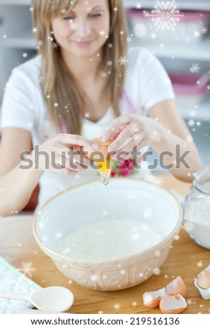 Attractive woman preparing a cake in the kitchen with snow falling - stock photo