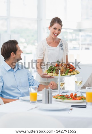 Attractive woman presenting a roast chicken to her family - stock photo