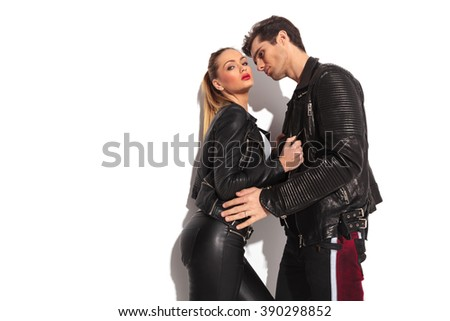 attractive woman pulling her lover close to her , in studio. passionate young couple  - stock photo