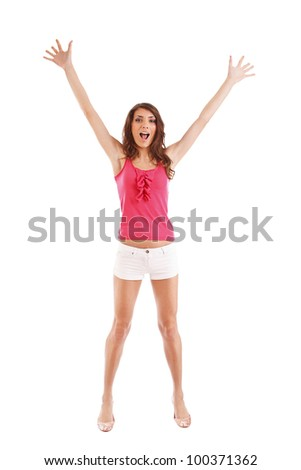 Attractive woman raises her arms overhead in celebration after hearing some good news - stock photo