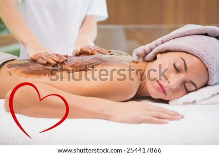 Attractive woman receiving chocolate back mask at spa center against heart - stock photo