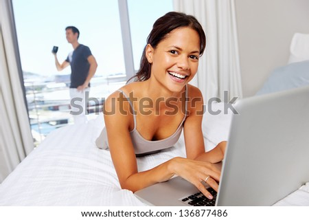 attractive woman relaxes at home using laptop computer while husband drinks coffee. leisure couple - stock photo