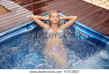 attractive woman relaxing in a whirlpool jacuzzi - stock photo