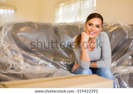 attractive woman relaxing on new bubble wrapped couch in the new house - stock photo
