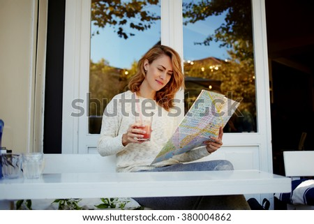 Attractive woman resting in sidewalk cafe and searching locations on city map during her spring vacation, young female tourist exploring atlas while drinking juice and relaxing in modern coffee shop - stock photo