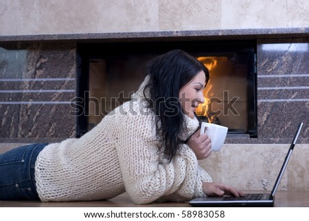 Attractive woman rests at fireplace - stock photo