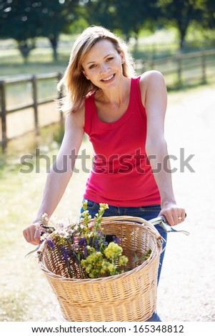 Attractive Woman Riding Bike Along Country Lane - stock photo
