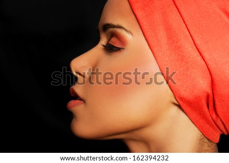 Attractive woman's profile in turban. Closed eyes. Isolated on black.  - stock photo