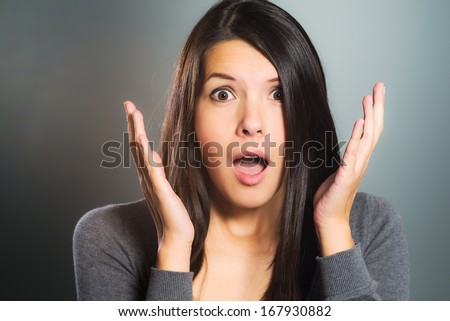 Attractive woman screaming in terror with her hands to her cheeks, mouth open and frightened wide eyes, close up facial portrait - stock photo