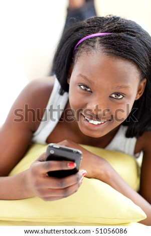 Attractive woman sending a text lying on a sofa in the living-room