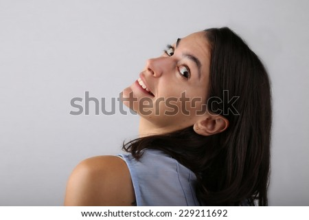 Attractive woman shot from her back leaning her head back toward the camera in a studio - stock photo