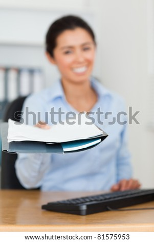 Attractive woman showing a sheet of paper to the camera at the office