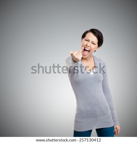 Attractive woman shows a vulgar, obscene finger gesture, isolated on grey - stock photo