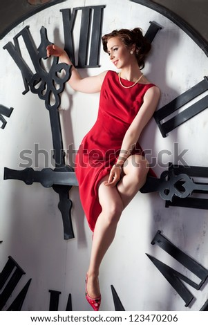 Attractive woman sitting on huge clock - stock photo