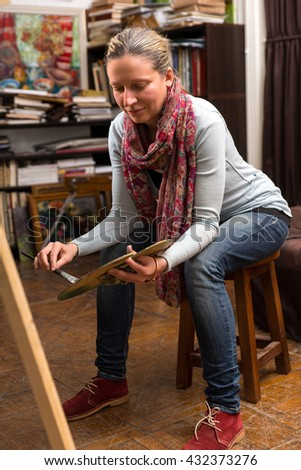 Attractive woman sitting painting in a studio or gallery holding a colorful artists palette and paintbrush in her hand as she assesses her canvas standing on an easel - stock photo