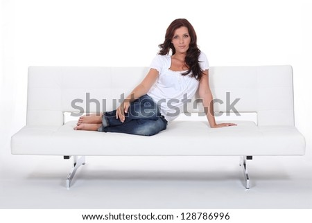 Attractive woman sitting with her feet up on a modern white sofa