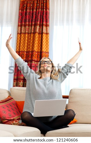 attractive woman sitting with laptop and stretching her arms - stock photo