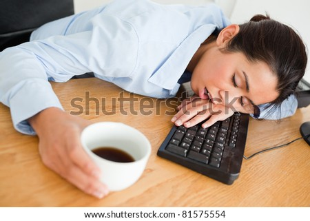 Attractive woman sleeping on a keyboard while holding a cup of coffee at the office - stock photo