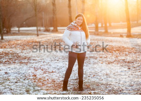 Attractive woman smiling in the park in sunlight of sunset sun, copyspace - stock photo