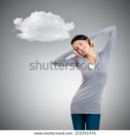 Attractive woman stretches herself, grey background - stock photo