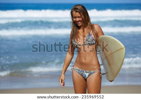 Attractive woman surfer having fun laughing walking with surfboard at sunny day, beautiful sports bikini model cheerful on summer travel vacation engage water sports, teenager girl in swimsuit - stock photo
