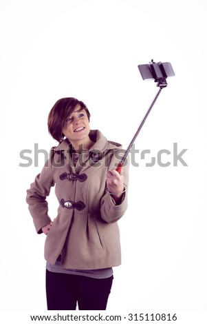 Attractive woman taking a selfie with a selfie stick - stock photo