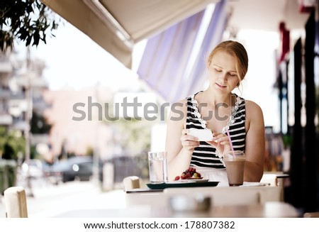 Attractive woman taking picture of a pastry on her smart phone as she sits at a table at an open-air restaurant enjoying refreshments. Instagram style color toned. - stock photo