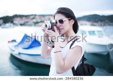 Attractive  woman  taking pictures with vintage retro camera laughing and smiling happy during summer holiday vacation travel.Seaside marine deck in Croatia.Island Korcula - stock photo
