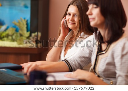 Attractive woman talking on her mobile in a business meeting while sitting alongside a female colleague - stock photo