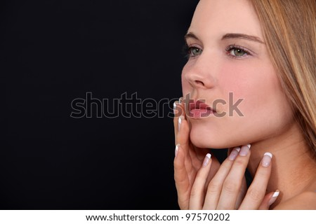 Attractive woman touching face - stock photo