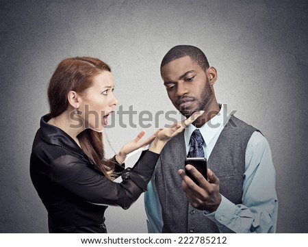 Attractive woman trying to bring attention of young handsome man ignoring her looking skeptical at smartphone reading text message grey wall background. Phone addiction concept. Human face expressions - stock photo