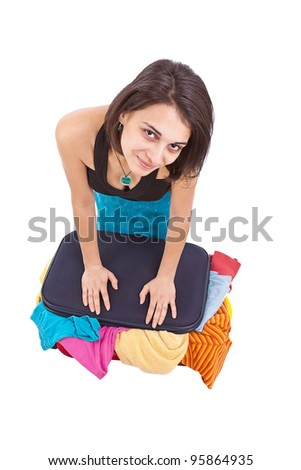 Attractive woman trying to close her suitcase, isolated on white