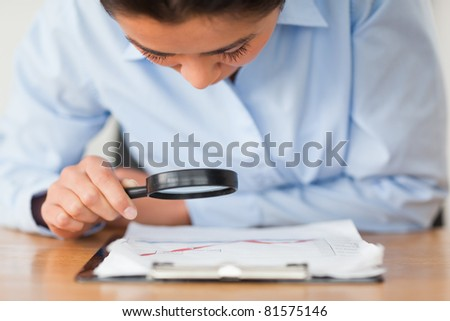 Attractive woman using a magnifying glass at the office - stock photo