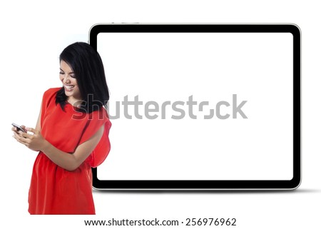 Attractive woman using a mobile phone while standing near a whiteboard in the studio - stock photo