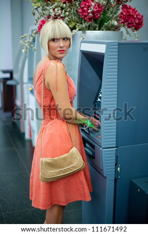 attractive woman using atm machine for cash - stock photo
