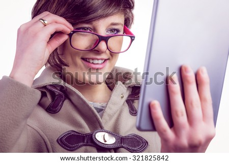 Attractive woman using her tablet pc in studio - stock photo