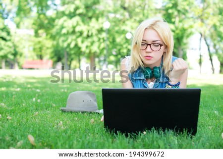 Attractive woman using laptop in the park lying on the green grass - stock photo