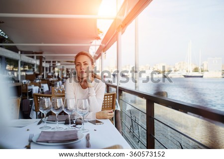 Attractive woman waiting for her order while enjoying calm autumn day in restaurant near the sea, young female thinking about something good while waiting for her boyfriend in modern open air cafe - stock photo