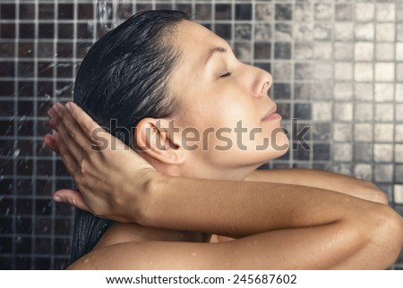 Attractive woman washing her hair in the shower rinsing it off under the spray of water with her head tilted back and eyes closed in a hair care, beauty and hygiene concept - stock photo