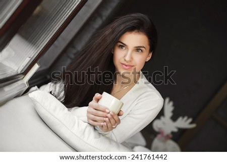 Attractive woman with a cup of coffee on the bed. Beautiful Girl Drinking Tea sitting in front of the window Indoor. Woman with the Cup of Hot Beverage.  - stock photo