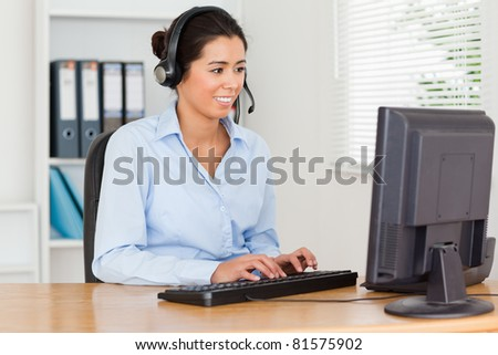 Attractive woman with a headset helping customers while typing on a keyboard at the office - stock photo